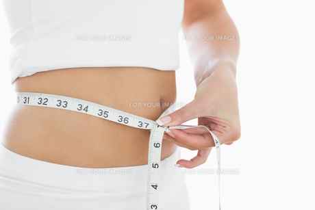 Closeup midsection of woman measuring waistの素材 [FYI00488768]