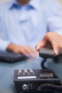 Closeup of man with telephone receiver at deskの写真素材 [FYI00488769]