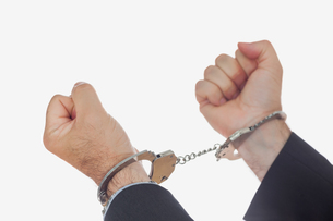 Man in handcuffs clenching fistsの写真素材 [FYI00488774]