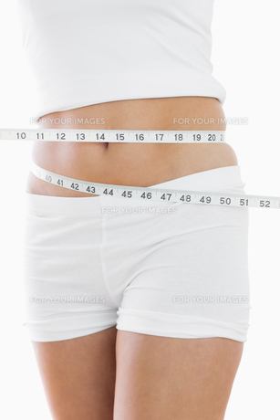 Closeup midsection of woman measuring waistの素材 [FYI00488782]