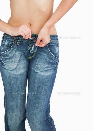 Midsection of slim woman buttoning jeansの写真素材 [FYI00488785]