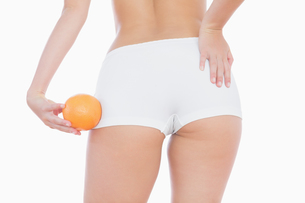 Woman in shorts holding orangeの写真素材 [FYI00488797]