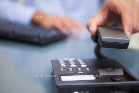 Man with telephone receiver at deskの写真素材 [FYI00488824]