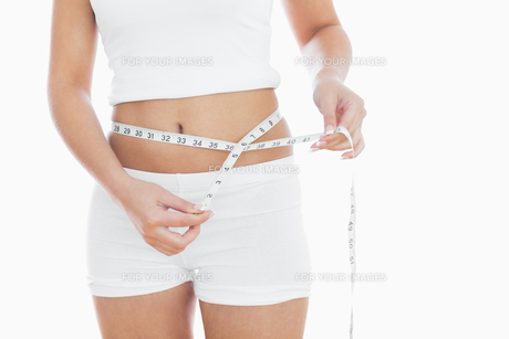 Midsection of woman measuring waistの写真素材 [FYI00488834]