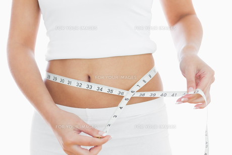 Midsection of woman measuring waistの写真素材 [FYI00488837]