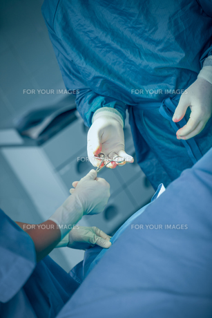 Doctor taking a scissors from the hand of a nurseの素材 [FYI00488840]