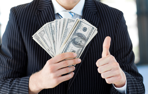 Businessman showing dollars with thumbs upの写真素材 [FYI00488847]