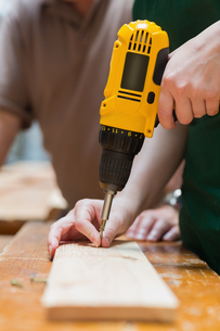 Drilling a hole in a wooden boardの写真素材 [FYI00488891]