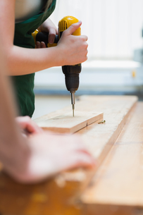 Drilling a hole in a wooden board on the workbenchの写真素材 [FYI00488892]