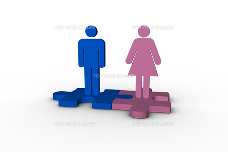 Blue and pink human figures over jigsaw pieces meshed togetherの写真素材 [FYI00488912]