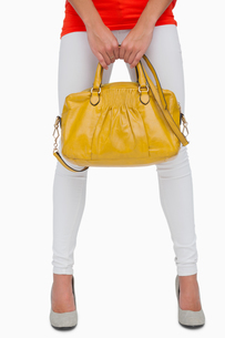 Woman in white leggings holding yellow bagの写真素材 [FYI00488925]