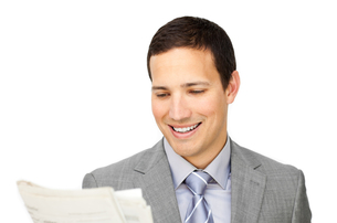 Smiling businessman reading a newspaperの写真素材 [FYI00488953]