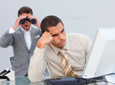 Young businessman getting bored and his manager looking through binocularsの写真素材 [FYI00488954]