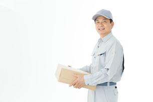 荷物を持った作業着男性の写真素材 [FYI00489045]