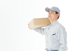 荷物を持った作業着男性の写真素材 [FYI00489046]