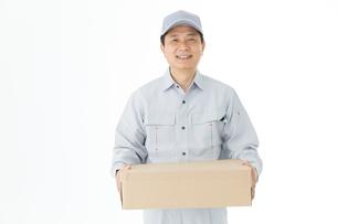 荷物を持った作業着男性の写真素材 [FYI00489055]