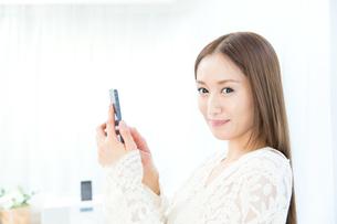 携帯電話を使う女性の写真素材 [FYI00490189]