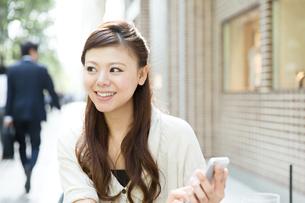 カフェで携帯電話を使う女性の写真素材 [FYI00490737]