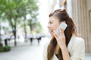 カフェで携帯電話を使う女性の写真素材 [FYI00490738]