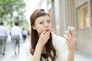 カフェで携帯電話を使う女性の写真素材 [FYI00490741]