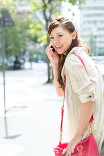 屋外で携帯電話を使う女性の写真素材 [FYI00490867]