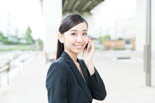 携帯電話を使う屋外のビジネスウーマンの写真素材 [FYI00490945]