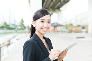 タブレットPCを使う屋外のビジネスウーマンの写真素材 [FYI00490948]