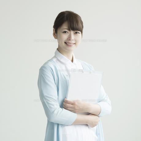 カルテを持ち微笑む看護師の写真素材 [FYI00491253]