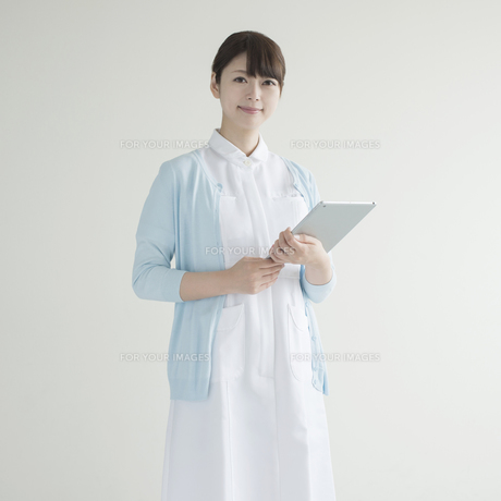 タブレットPCを持ち微笑む看護師の素材 [FYI00491262]