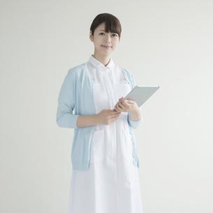 タブレットPCを持ち微笑む看護師の写真素材 [FYI00491262]