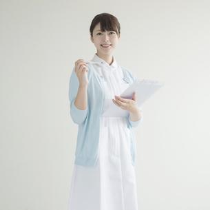 体温計とカルテを持ち微笑む看護師の素材 [FYI00491264]