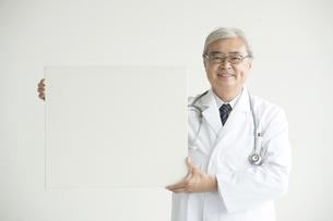 メッセージボードを持ち微笑む医者の写真素材 [FYI00491277]
