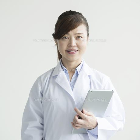 タブレットPCを持ち微笑む女医の素材 [FYI00491280]