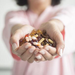 大量の薬を持つ患者の手元の素材 [FYI00491285]
