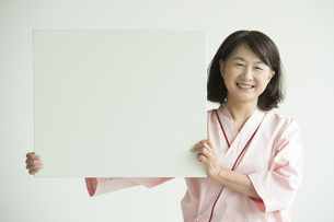メッセージボードを持ち微笑む患者の写真素材 [FYI00491289]