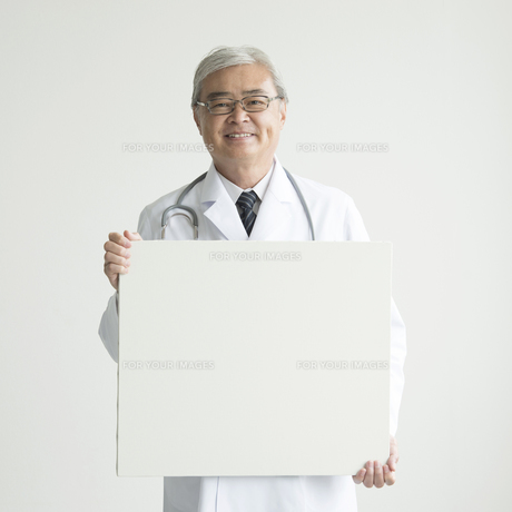 メッセージボードを持ち微笑む医者の写真素材 [FYI00491290]