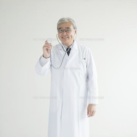 聴診器を持ち微笑む医者の写真素材 [FYI00491296]