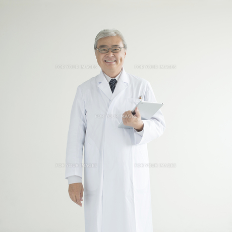 タブレットPCを持ち微笑む医者の写真素材 [FYI00491299]