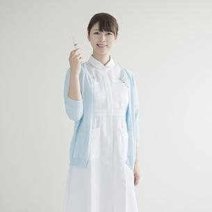 注射器を持ち微笑む看護師の素材 [FYI00491336]