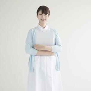 カルテを持ち微笑む看護師の写真素材 [FYI00491352]