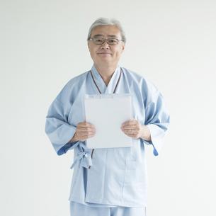 カルテを持ち微笑む患者の写真素材 [FYI00491360]