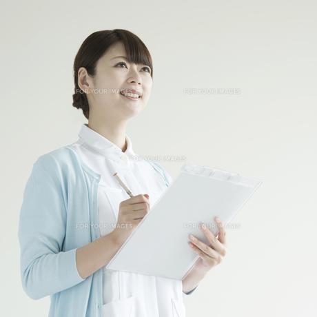 カルテを持ち微笑む看護師の写真素材 [FYI00491367]