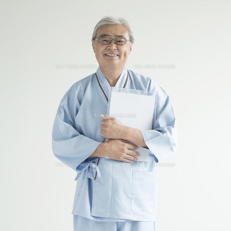 カルテを持ち微笑む患者の写真素材 [FYI00491369]