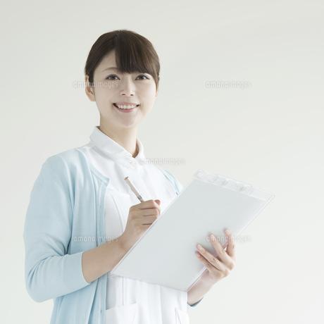 カルテを持ち微笑む看護師の写真素材 [FYI00491376]