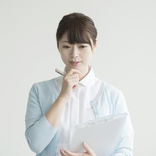 カルテを持ち考え事をする看護師の写真素材 [FYI00491378]