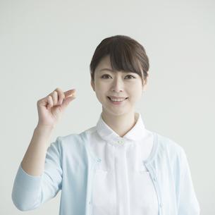 薬を持ち微笑む看護師の写真素材 [FYI00491383]
