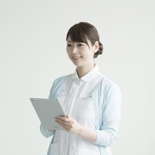 タブレットPCを持ち微笑む看護師の写真素材 [FYI00491384]