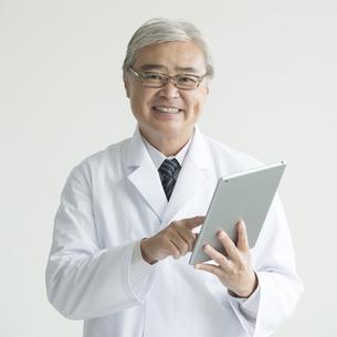 タブレットPCを持ち微笑む医者の素材 [FYI00491391]