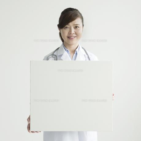 メッセージボードを持ち微笑む女医の写真素材 [FYI00491408]
