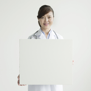 メッセージボードを持ち微笑む女医の素材 [FYI00491408]